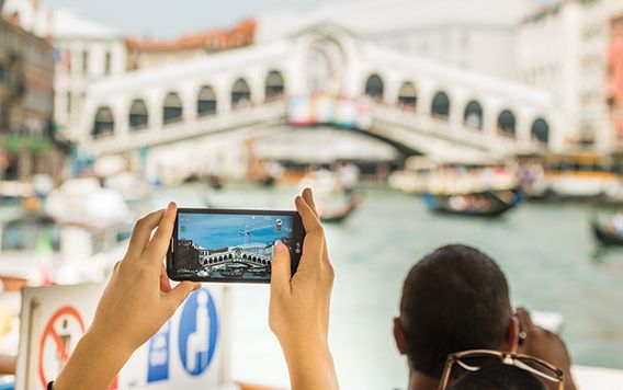 persons hands holding a phone taking a video of a bridge in venice italy
