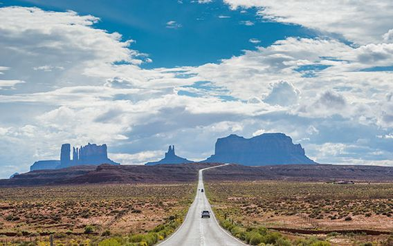 cars driving along road towards monument valley in arizone