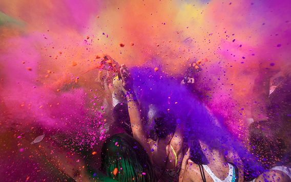 purple and pink powder being thrown in air by group of people