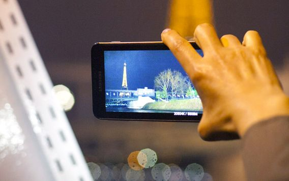 close up of hand holding a camera taking a photo of the eiffel tower