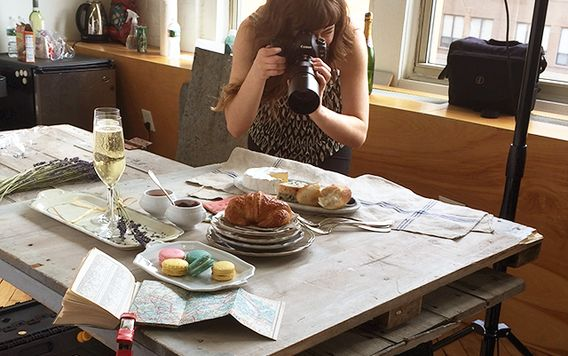 woman taking close up photo of classic french dishes on wooden slab