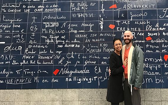 couple standing in front of the wall of love in paris france