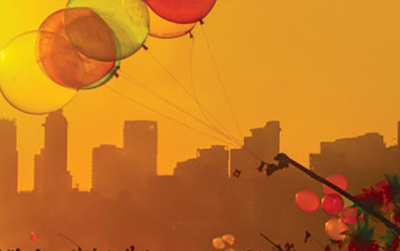 colored kites flying above silhouettes of people in front of jaipur skyline