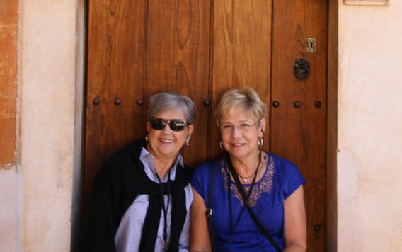 two travelers sitting infront of a wooden door at the alhambra in spain