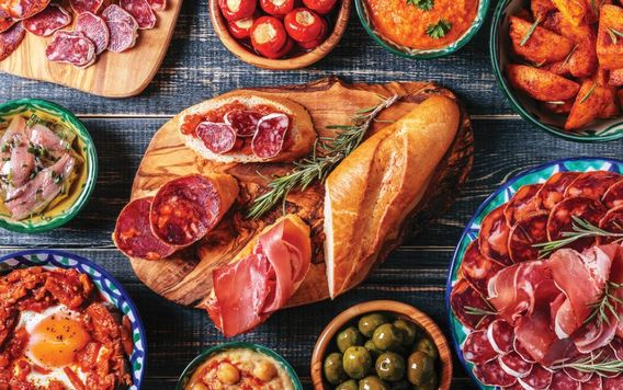 birds eye view of spanish tapas on a blue table