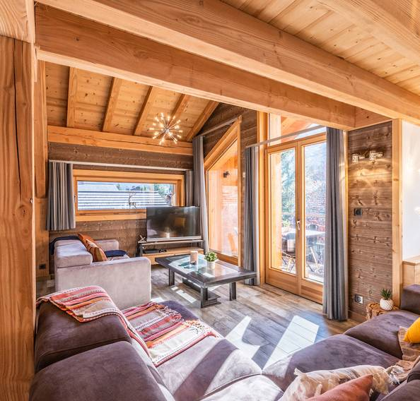 Living room with grey couches and TV at Etoile accommodation in Morzine