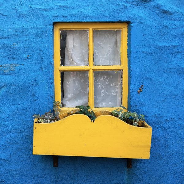 A homes bright yellow window on a rustic blue wall in Kinsale Ireland