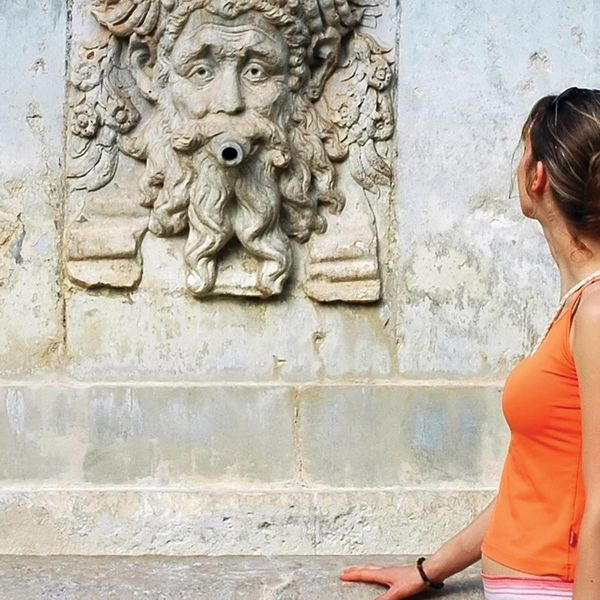 woman in orange tank top looking at stone carved mural