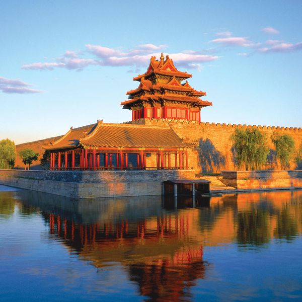 corner tower of imperial palace in the sunset reflecting in water in beijing china