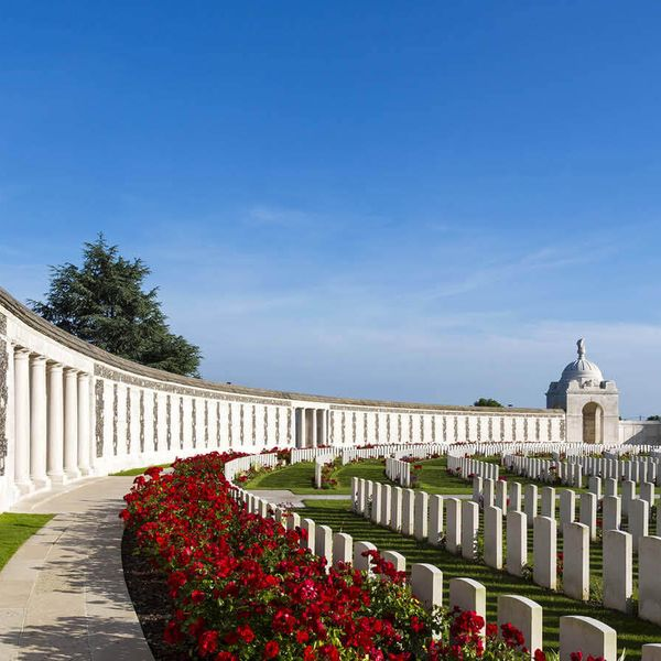 white graves surrounded by red flowers in tyne cot cemetery in belgium