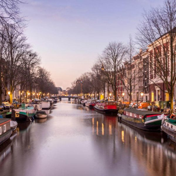 boats docked in canal in amsterdam on a winter day