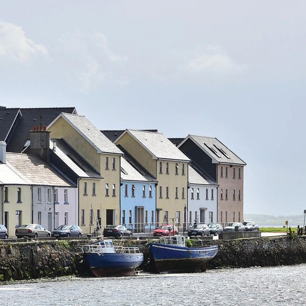 houses lined up along harbor in galway ireland on cloudy day