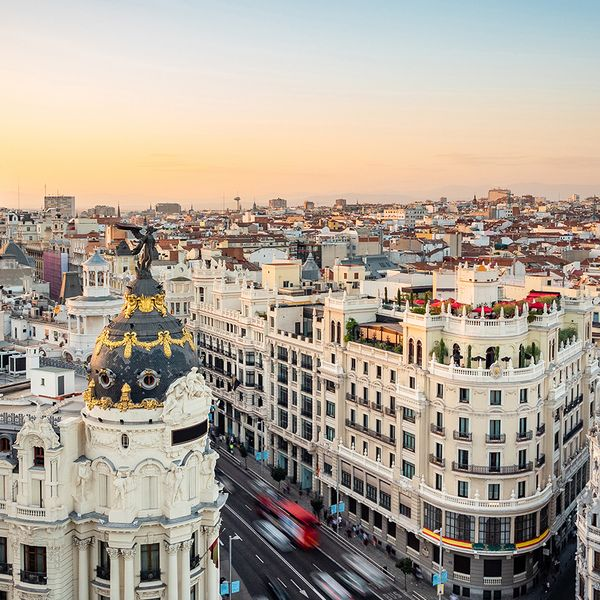 sunset over landmark buildings on gran via street in madrid spain