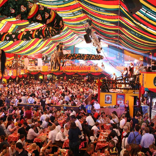 people celebrating oktoberfest in colorful tent