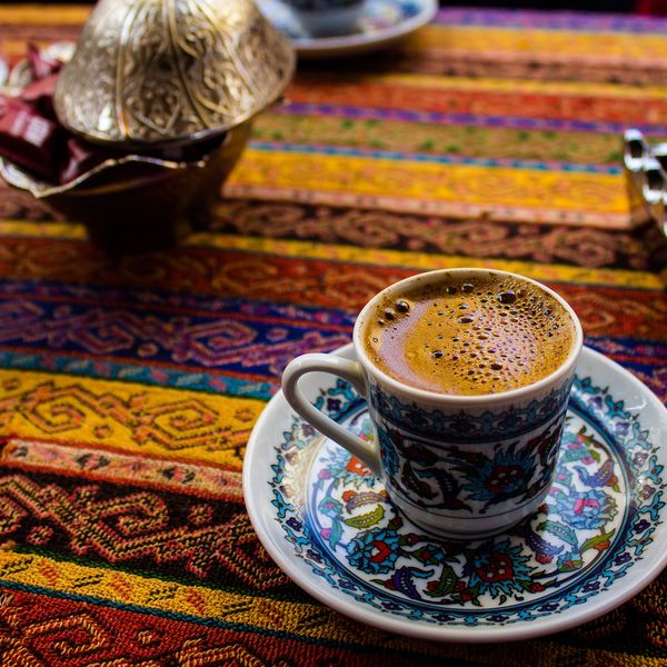 blue saucer with a cup of turkish coffee on a multicolored tablecloth