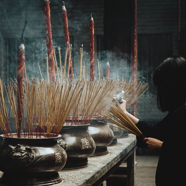 woman lighting incense at a temple in ho chi minh city vietnam