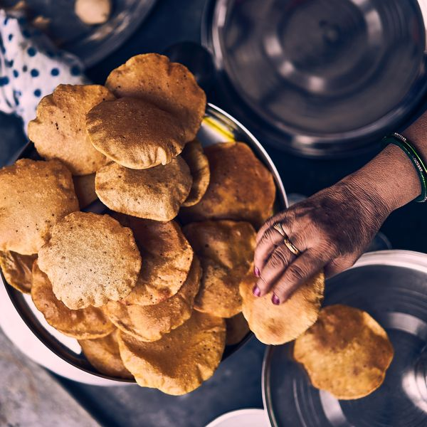 hand of a woman serving fried indian bread called poori