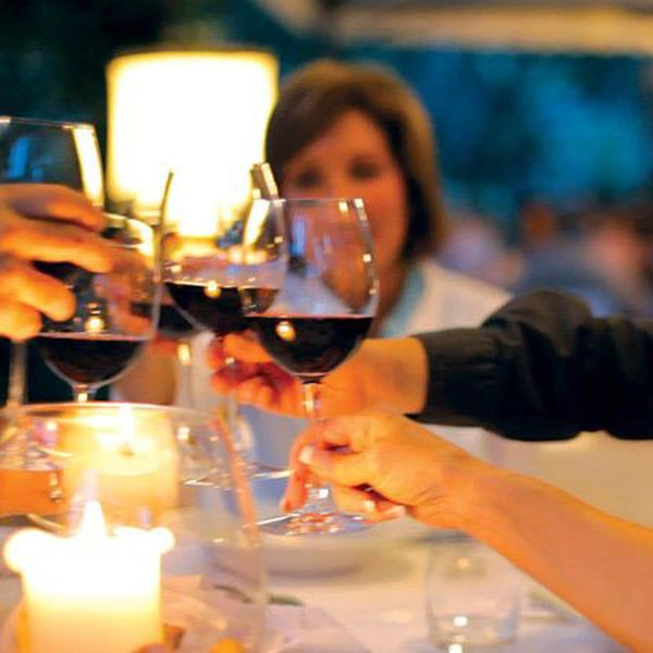 people at a table clinking wine glasses at a table
