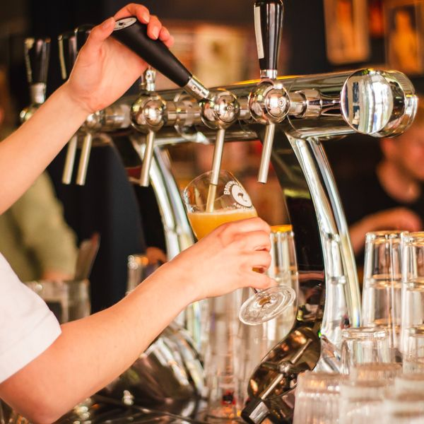 a bartender pouring a pint of beer in an irish bar
