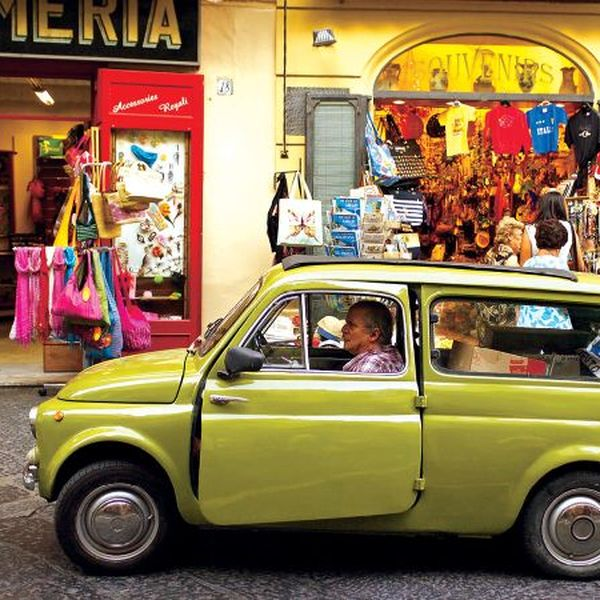 an old green car parked in front of a store in italy