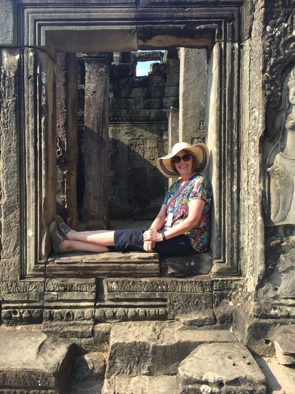 A woman sitting in a doorframe of some temple ruins, wearing a hat and smiling
