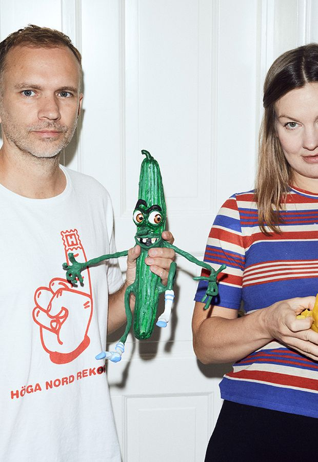 two artists standing in front of a white door, one holding a plasticine cucumber with a disgruntled face and another holding an uneven ball of yellow clay