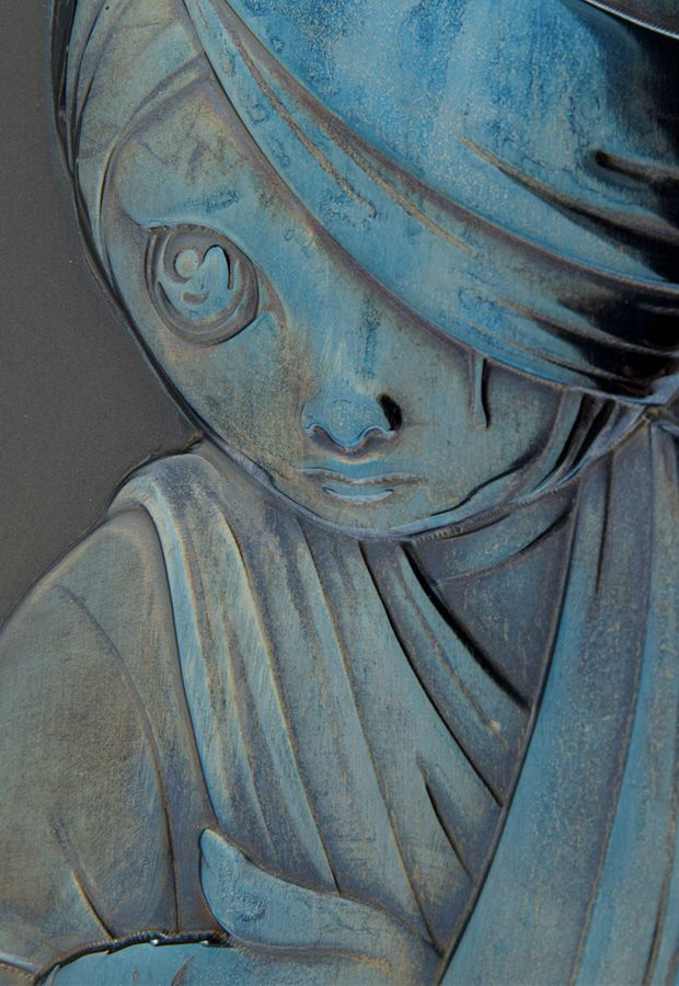close up image of a carved steel relief sculpture of a young boy in bandages with a blue-toned iridescent finish