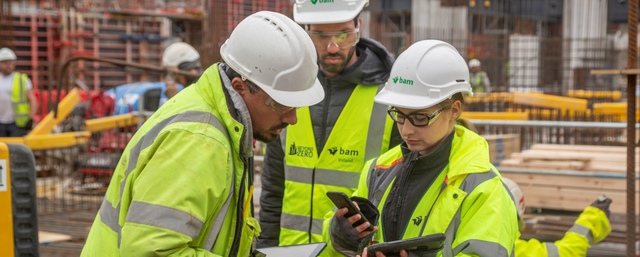 Construction workers on site using construction management software to improve performance.