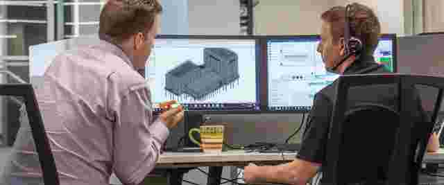 Two Construction Project Managers looking at models on computers and discussing streamlining processes with construction project management software.