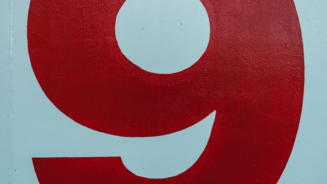 A picture of a red number 9 in red paint on a white wall.