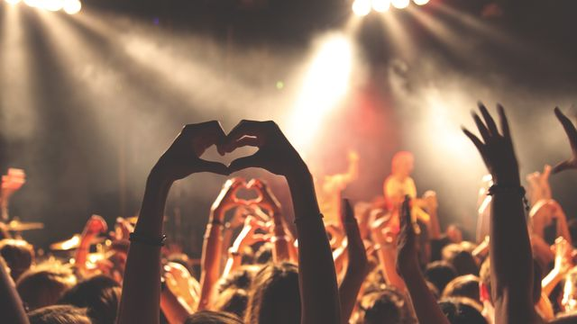 A picture of a large group of people with their hands in the air, some making a heart shape with their fingers, at a concert.