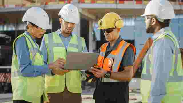 Four construction workers on site looking at construction management software to improve submittals tracking.