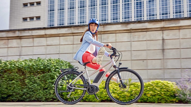 A Lady riding a Raleigh Motus ebike through the city