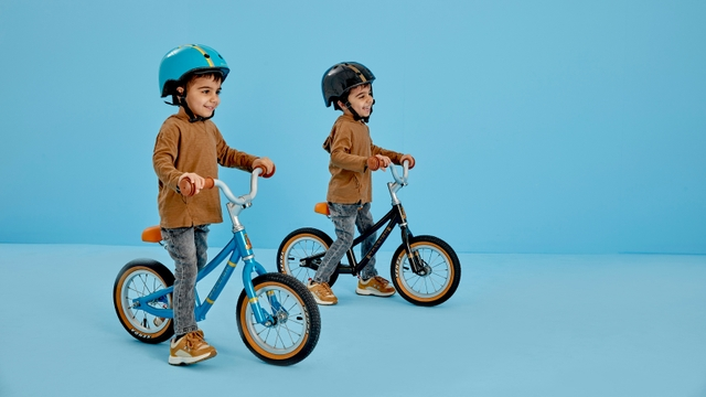 Two kids playing around on a Raleigh bike