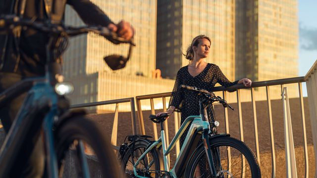 Vrouw naast e-bike E-Burst van Sparta bij zonsondergang