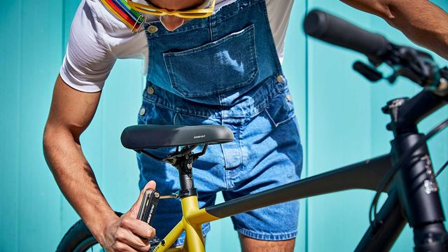 A man adjusting the seat height of A Raleigh Strada bike