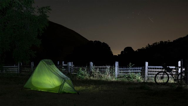 A bike parked next to a tent at night under the stars