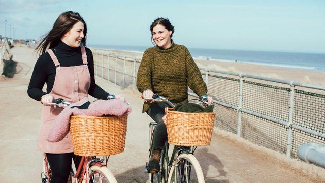Two women biking near the beach