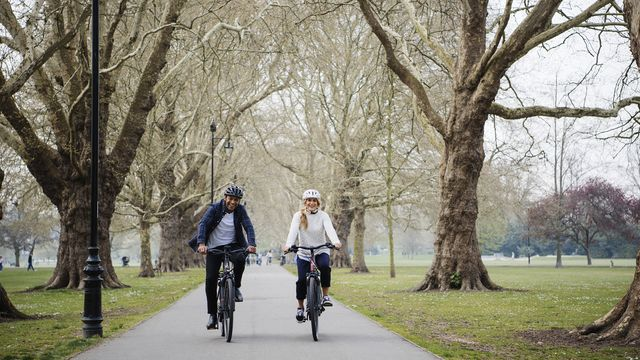Two people riding a bike during autumn