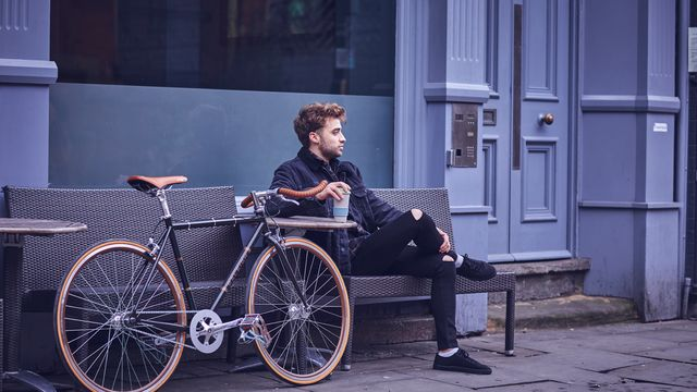 A man sitting outdoors drinking coffee next to his bike