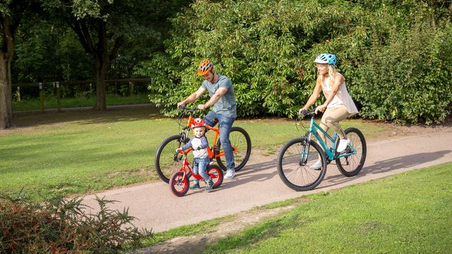 Man and woman biking with a kid in front
