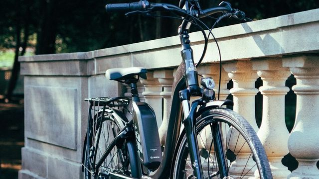 An electric Raleigh bike standing against a wall