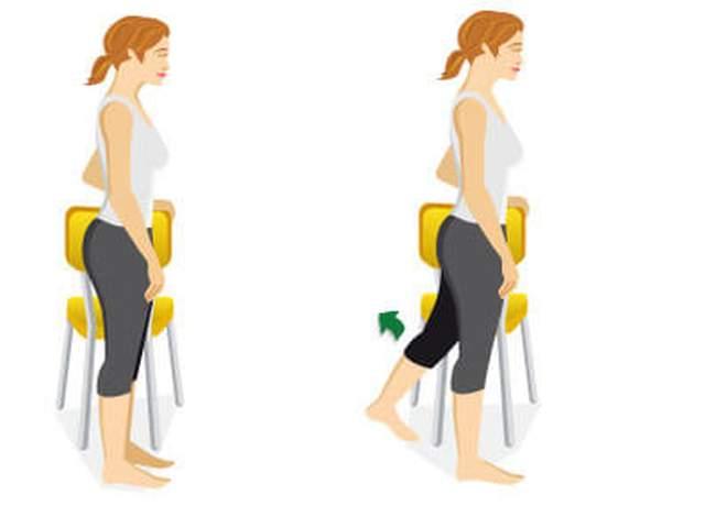 Frau stützt sich an Stuhllehne und fährt Bein mit gestrecktem Knie nach hinten