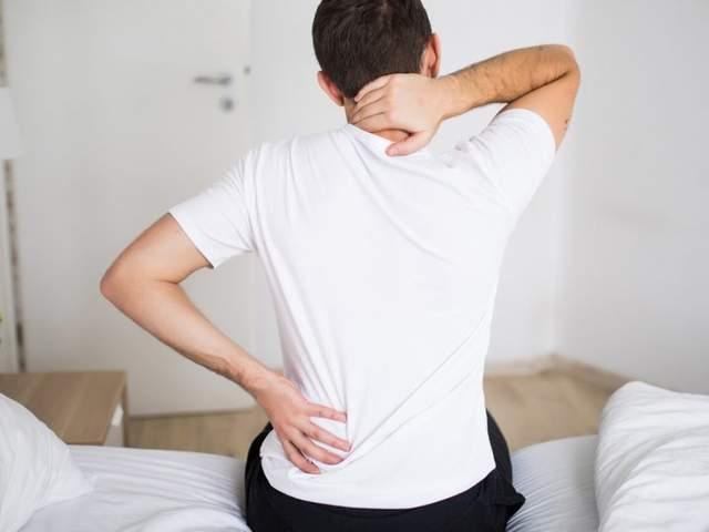 Mann fasst sich an schmerzende Sellen an Rücken und Nacken wegen Muskelkater