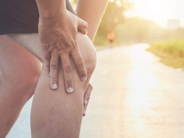 Mann hält sich beim Laufen auf der Straße das Knie aufgrund eines Erguss im Knie