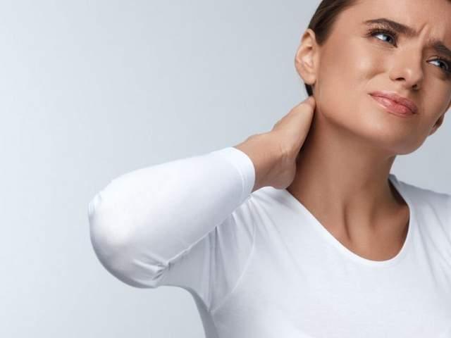 Frau fasst sich an Nacken aufgrund starker Verspannungen