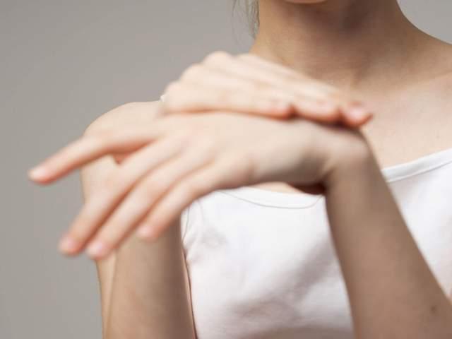 Frau fasst sich an Handgelenk da es knackt