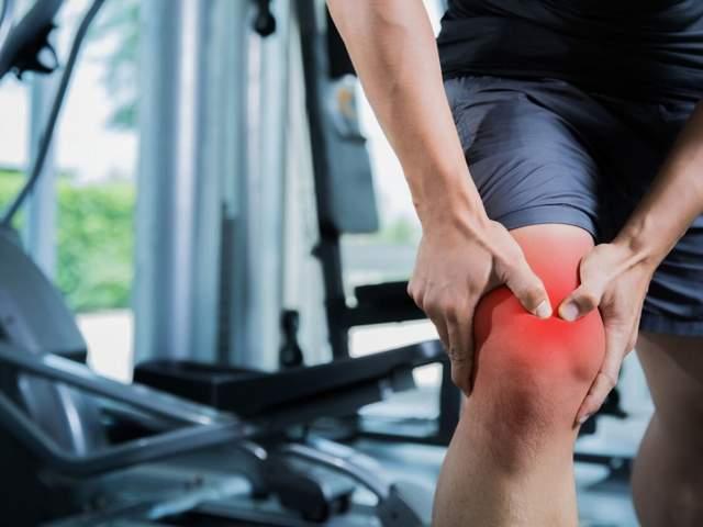 Mann im Fitnessstudio hat plötzliche Schmerzen am Knie aufgrund einer Gelenkschleimhautentzündung