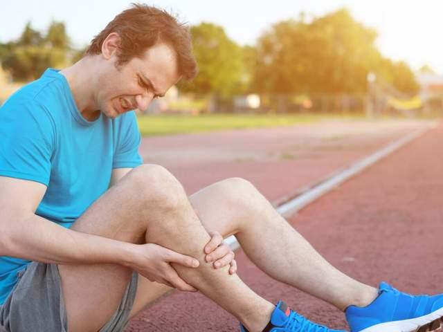 Mann sitzt auf Laufbahn und fasst sich an Wade aufgrund eines Wadenkrampfes