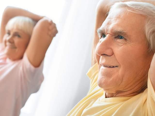 Älteres Ehepaar macht eine Übung zur Dehnung der Schultern